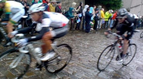 Cyclists riding up a cobbled hill