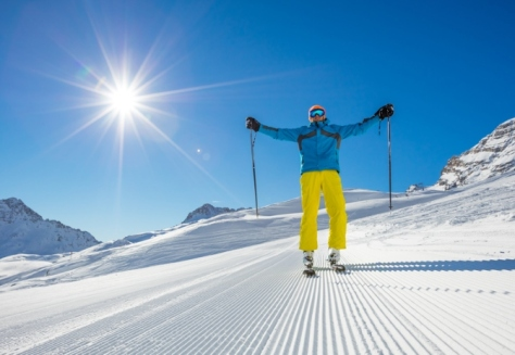 Skier on piste in sunny day with hands up. Skiing concept. Alpine ski resort in Zugspitze, Germany